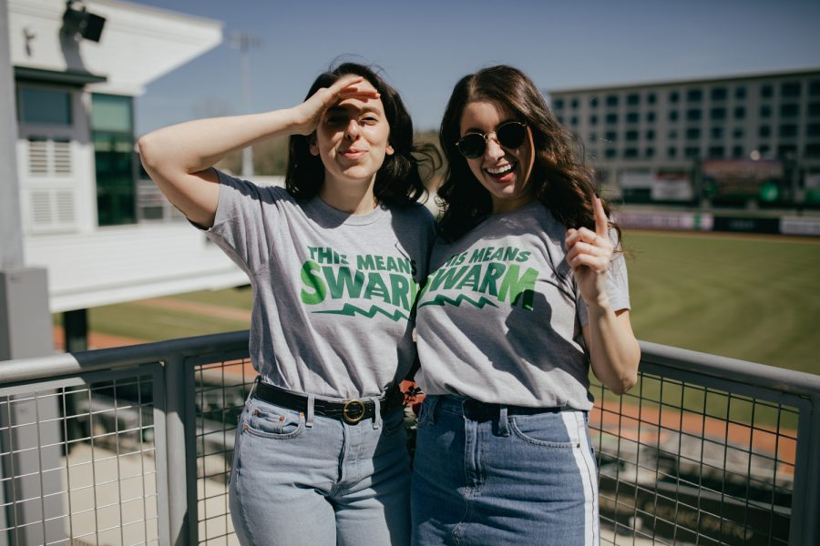 Two women wearing gray Augusta Green Jackets Swarm shirts and smiling at the ball park