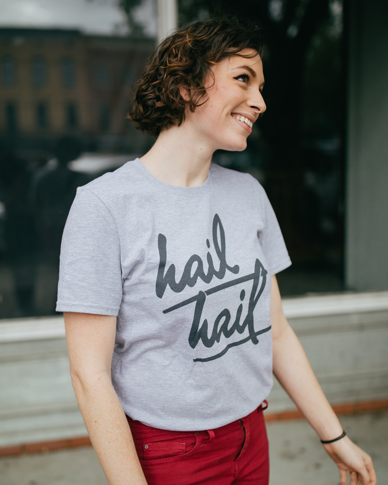 Woman wearing a gray Ann Arbor Michigan Hail Hail shirt with red jeans