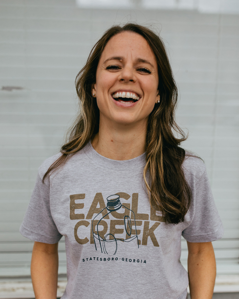Woman laughing wearing a gray Statesboro Georgia Eagle Creek shirt with a water jug on it
