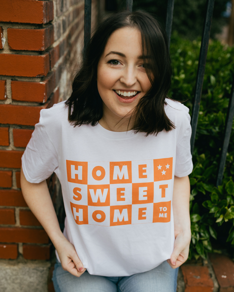 Woman laughing and wearing a white Knoxville Tennessee Home Sweet Home shirt