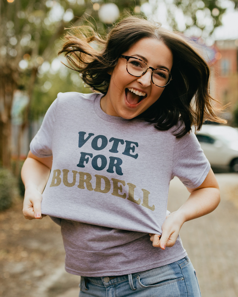 Woman jumping and wearing a gray Atlanta Georgia Vote for Burdell shirt