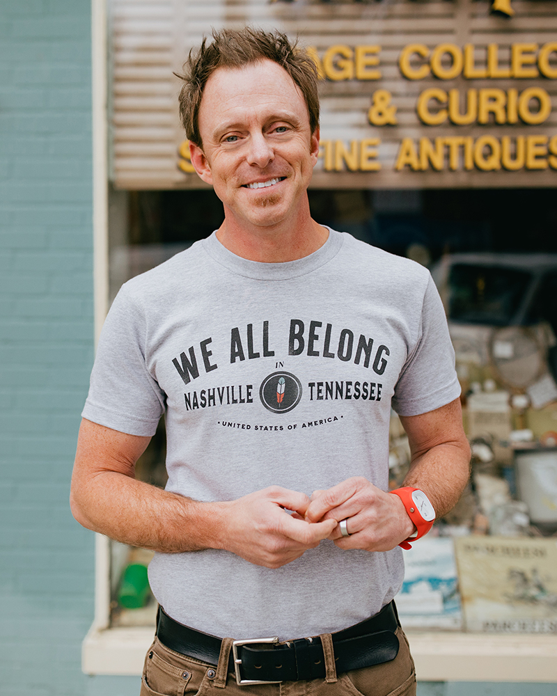 Man wearing gray We All Belong Nashville Tennessee shirt with brown pants