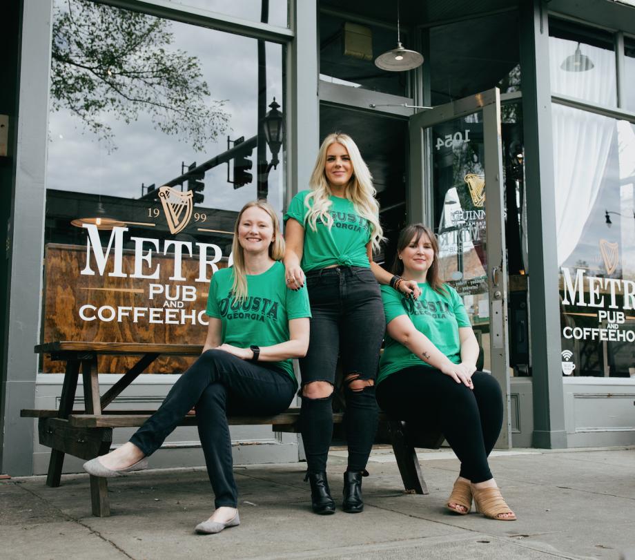 Three women wearing green Augusta Georgia St. Patrick's Day shirts and black pants