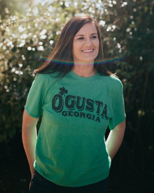 Woman wearing green Augusta Georgia St. Patrick's Day shirt with jeans