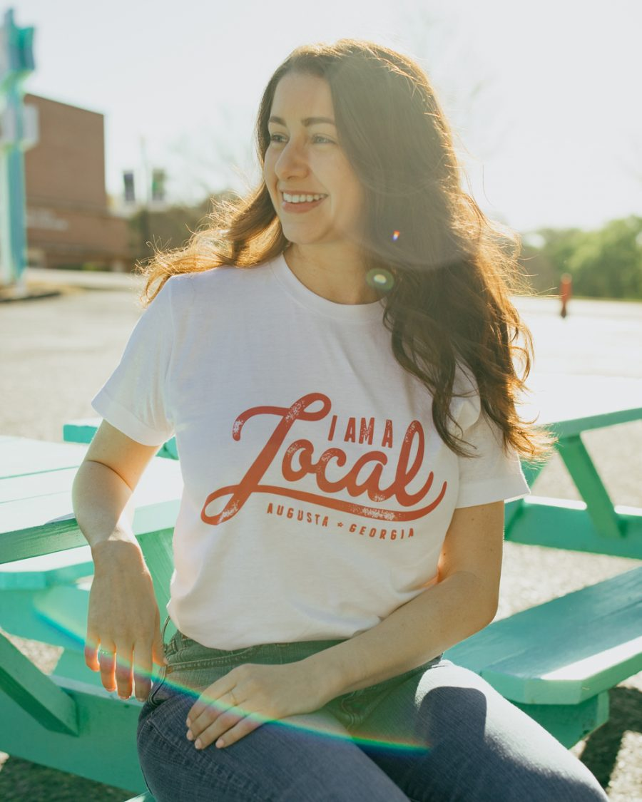 Woman wearing white local Augusta Georgia shirt with jeans