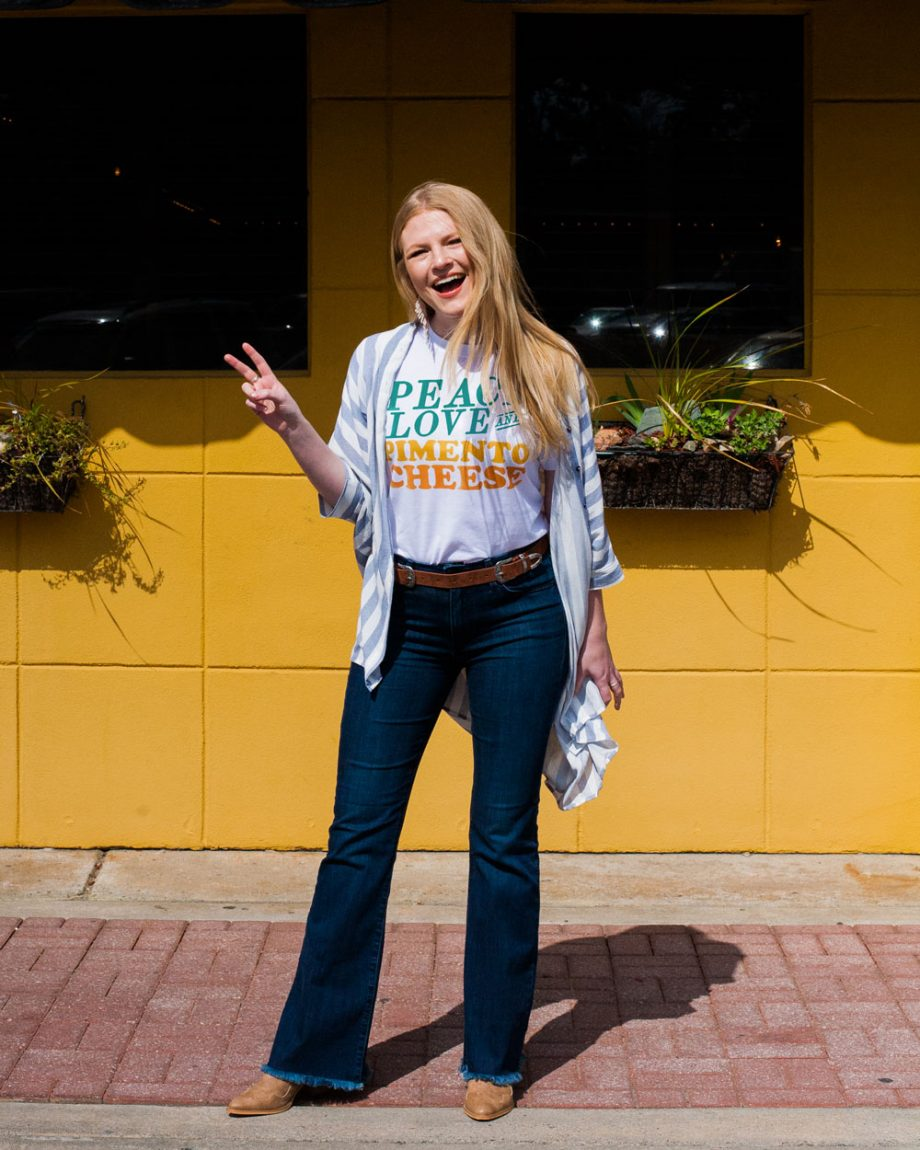 Woman wearing white Peace Love and Pimento Cheese shirt with jeans